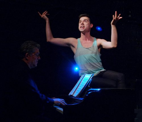 """Benjamin Dreier atop of the piano in a scene from """"Mad About the Boy"""" (Photo credit: Jonathan M. Smith)"""