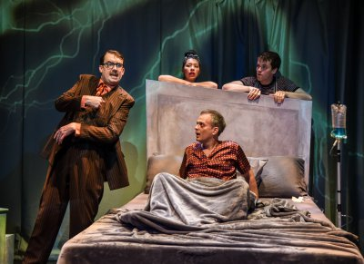 "Ian Gould, Rebeca Fong, Christopher Daftsios (in bed) and Andy Reinhardt in a scene from ""In Bed with Roy Cohn"" (Photo credit: Russ Rowland)"